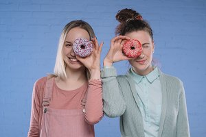 smiling young women covering eyes wi