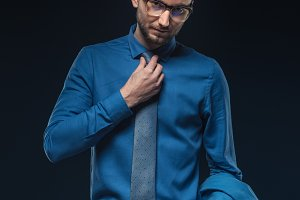 Young businessman in glasses fixing