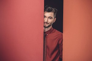 Smiling young man by red paper walls