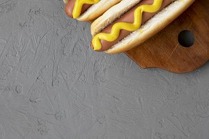 Tasty hot dogs with yellow mustard