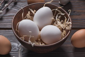 chicken eggs in bowl with straw and