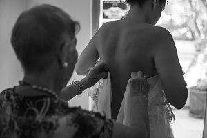 Bridesmaid preparing bride