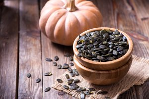 Pumpkin seeds on wooden background