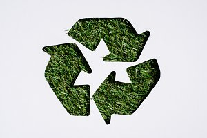 Top view of recycle sign with grass