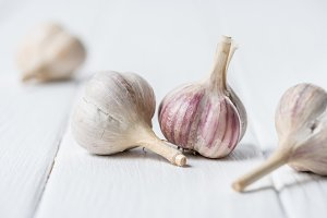 Ripe garlic heads on white wooden ta