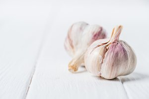 Two bulbs of ripe garlic on wooden t