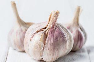 ripe garlic heads on white rustic ta