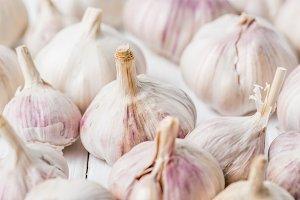 Ripe garlic bulbs on white kitchen t