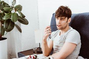 pensive man holding eyeglasses while