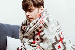 sick young man wrapped in blanket