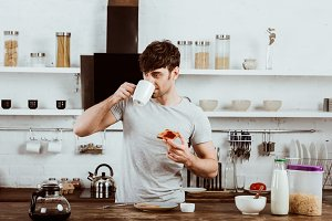 young man drinking coffee and eating