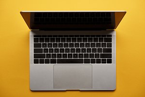 top view of opened laptop on yellow