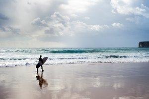 Surfer surfboard walking beach