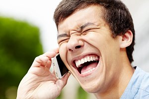 Laughing guy with smartphone closeup