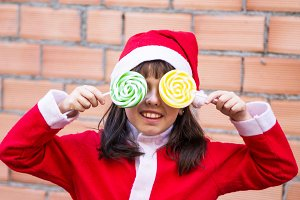 girl with santa hat and lollipop