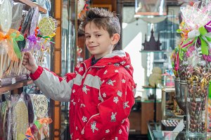 boy chooses lollipop in the candy st