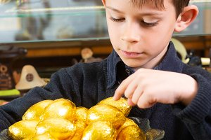 boy with chocolate eggs in the store
