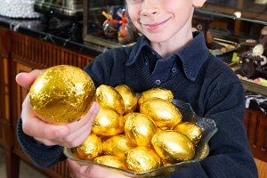 happy boy with chocolate eggs in the
