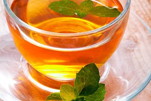 Glass cup of tea with mint on wooden