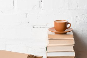 cup of coffee on pile of books near