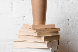 coffee to go on pile of books near w