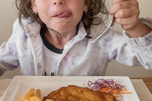 Girl eating breaded meat