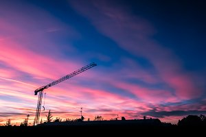 Construction crane over sunset sky