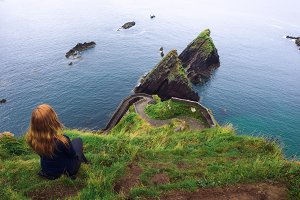 Girl sits on a cliff over the ocean