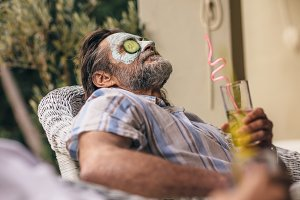 Retired man relaxing with clay mask