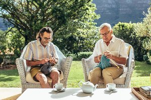 Two old men knitting