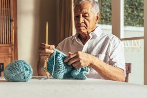Retired senior man knitting
