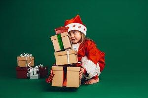 Kid dressed as santa lifting gift