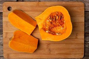 Sliced raw orange pumpkin on wooden