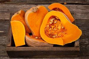 Sliced raw orange pumpkin in wooden