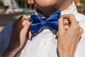 Bride Fixing Bow Tie Of Groom