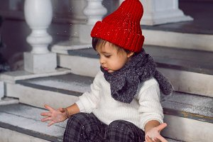 child in a white sweater and a red