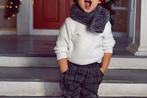 boy in a sweater and a hat stands on