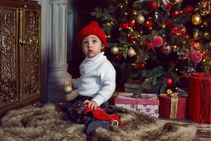 baby boy sitting next to Christmas
