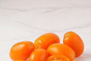 Orange tomatoes on white marble