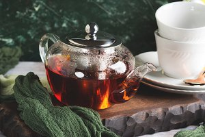 Hot tea in glass tea pot over green