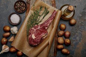 raw rib eye steak on baking paper wi