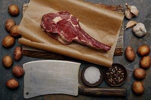 flat lay with raw rib eye steak on b