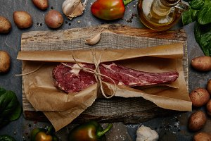 raw rib eye steak wrapped in baking