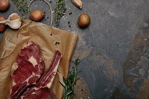 flat lay with raw rib eye steaks on