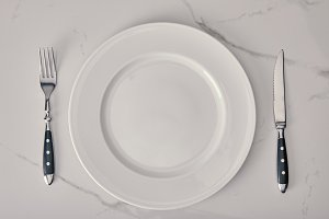 empty plate with fork and knife on w