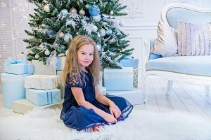 Cute girl sitting near Christmas