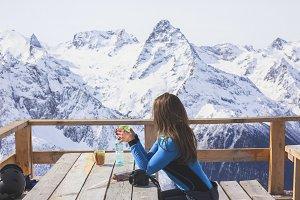 Woman drinking tea on mountain.