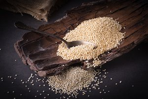 Dried quinoa grains, on a wood.