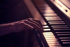 male hands on the piano keys closeup