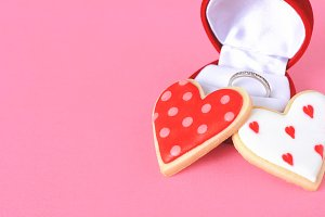 Two heart cookies and wedding rings